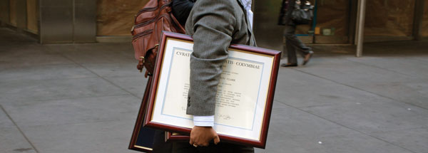 lawyer carrying framed diplomas under his arms