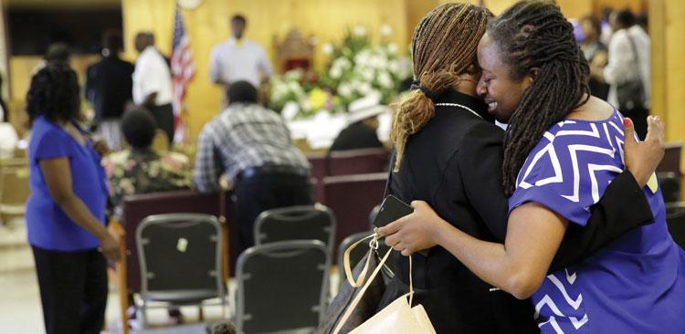 Two women hug inside a church