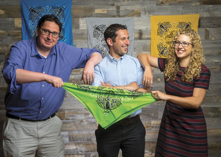 Three people pulling on a bandana