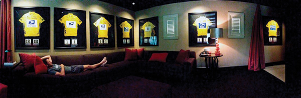 Lance Armstrong reclining on a couch with all 7 of his jerseys from each of his wins