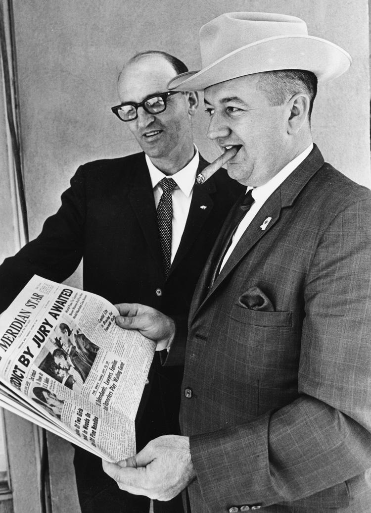 two men holding newspaper, one smoking cigar