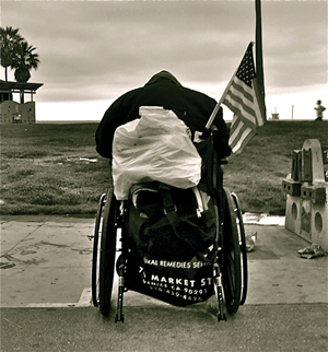 homeless veteran in a wheelchair with an American Flag on Venice Beach, California