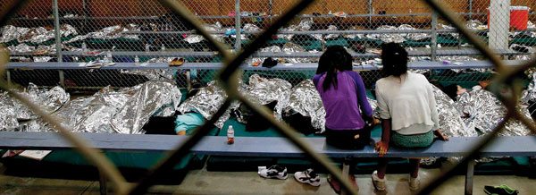 two young girls sit in a caged area