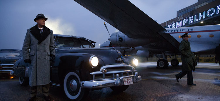 Tom Hanks next to 50s car and plane