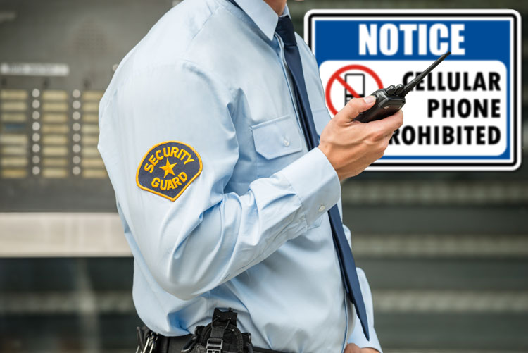 Security guard in front of a sign prohibiting cell phones.