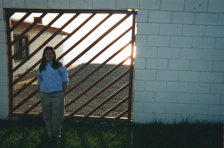 Chelsea as a teen standing in front of a barred gate and high cinderblock wall