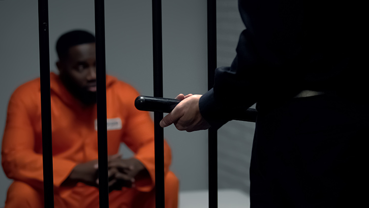 Man behind cell bars and a policeman holding a baton