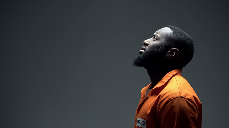 Man in prison jumpsuit looks up to the sky