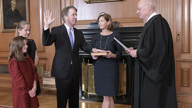Judge swears in Kavanaugh as family looks on.
