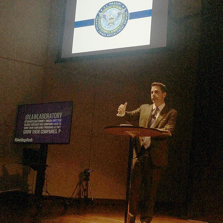 Blanco at podium below projected Treasury logo.