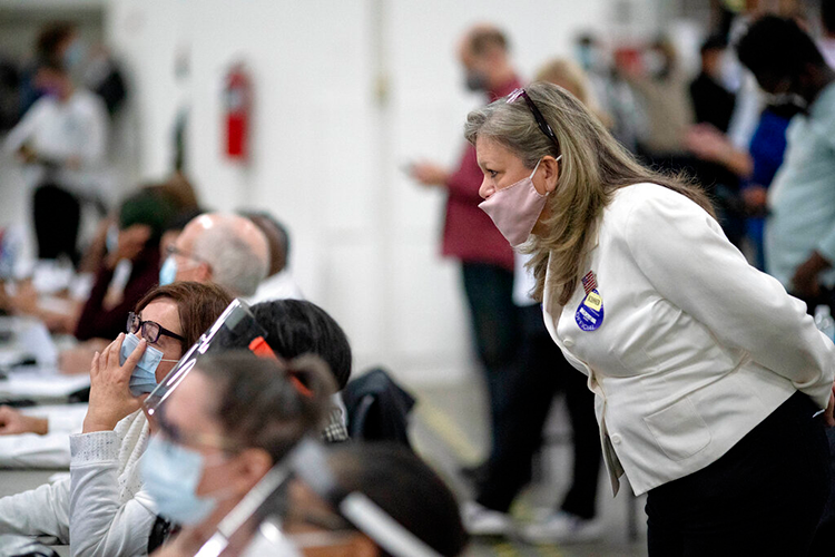 Woman looks over the shoulder of election workers