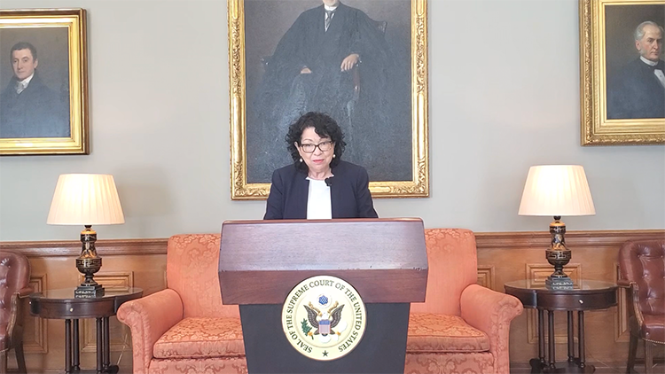 Sonia Sotomayor stands at a podium in front of oil paintings of Supreme Court justices