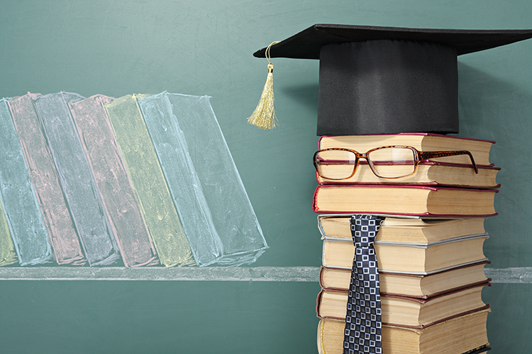 Stack of books dressed in a grad cap, tie and glasses, standing in front of a chalkboard