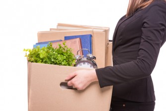 Woman holding box of office supplies.
