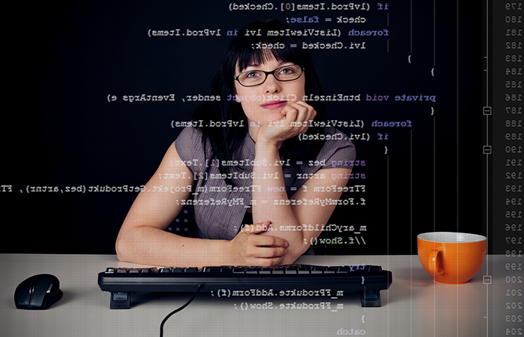 Woman at desk with computer code.