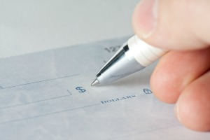 hand with pen writing a check