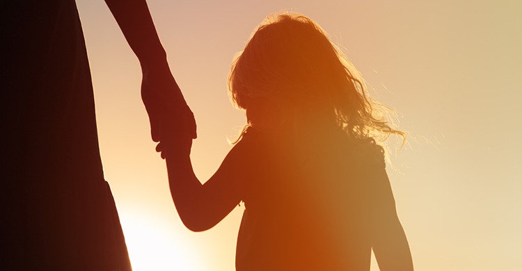 child backlit by sun holding an adult's hand