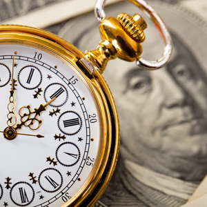 Pocketwatch on top of a 100 dollar bill