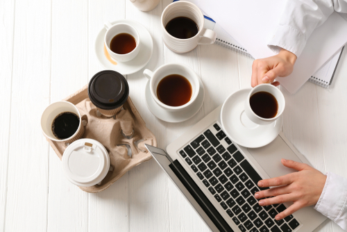 Businesswoman with a lot of empty cups of coffee working at table