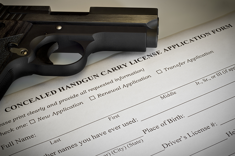 Handgun on top of a black concealed-carry-permit application form