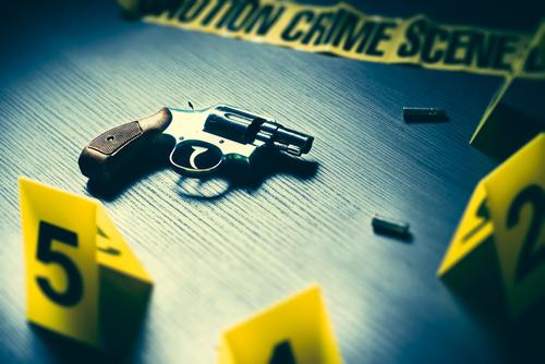crime scene with tape and gun