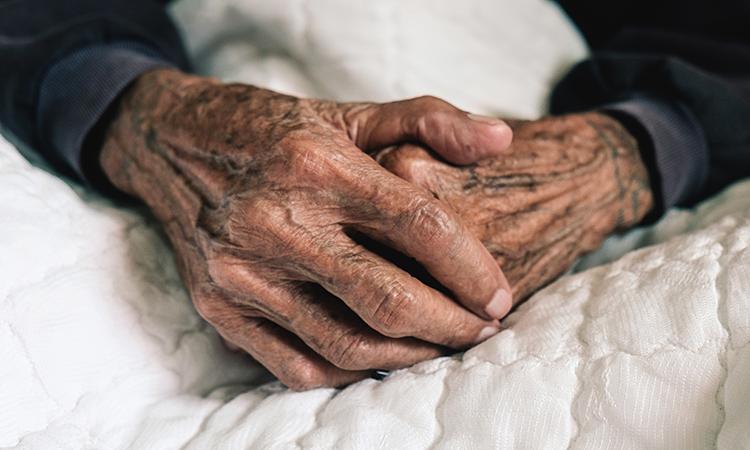 elderly man's hands as he lies in bed