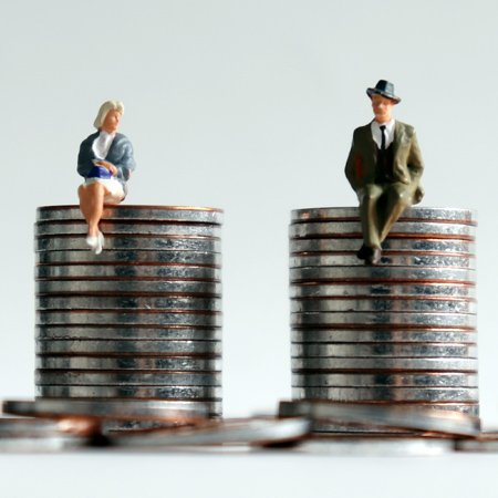 a woman and a man sitting on equally tall stacks of coins