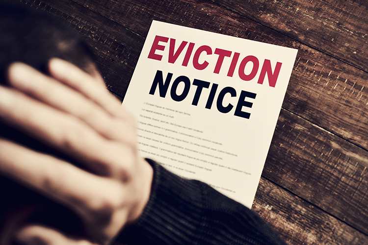 The man holds his head in his hands while looking at an eviction notice