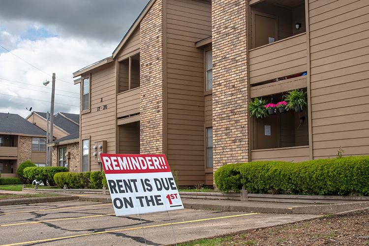 A sign in front of an apartment complex reminding that the rent is due