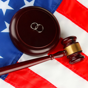 Gavel and wedding rings on top of a US flag