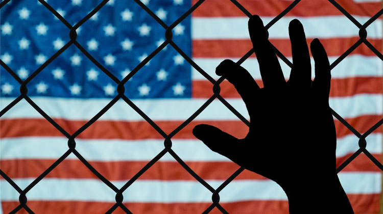 Hand and a chain link fence in front of the US flag