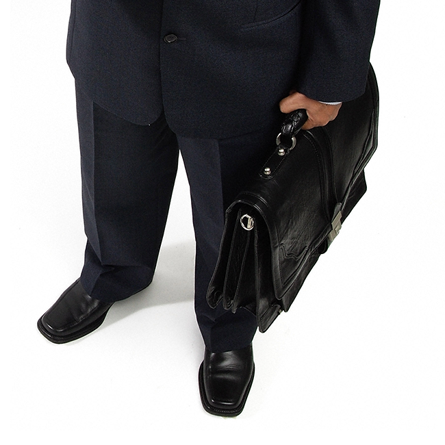 a man's lower body in business clothes with his hand holding a briefcase