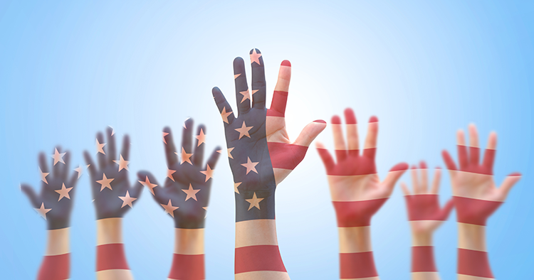 hands raised as if voting with the american flag projected onto them