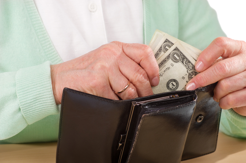 hands older woman holding wallet with money