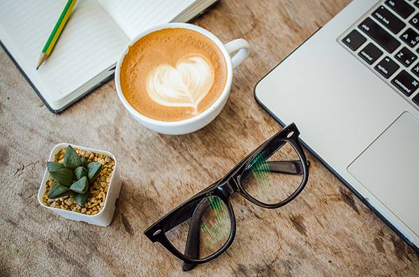 Workspace with a heart drawn in a coffee cup.