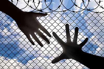immigration fence and two hands