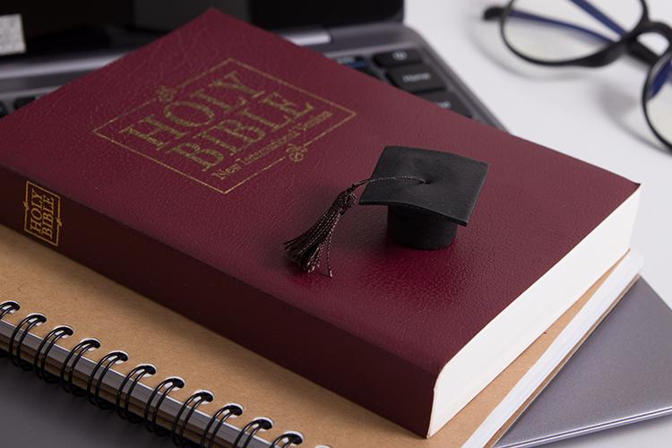 Laptop, holy bible and graduation cap