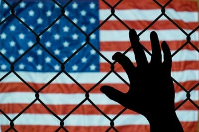 Child's hand on a fence looking at US flag