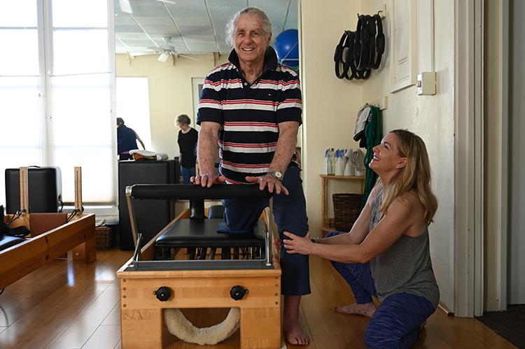man exercising with female teacher's help