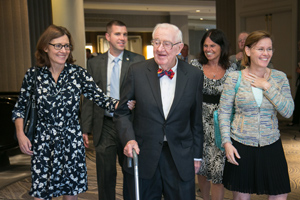 John Paul Stevens enters the room accompanied by a group of people