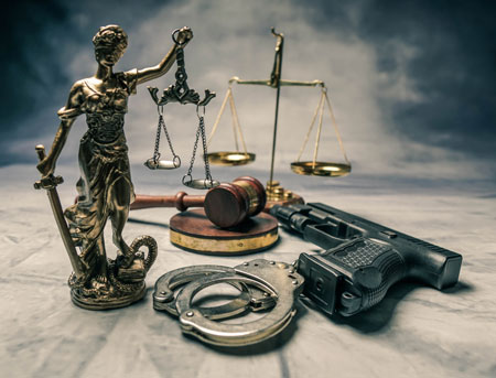 Scales of justice and a handgun and handcuffs.