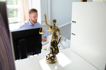 man typing on a computer with lady justice in the foreground