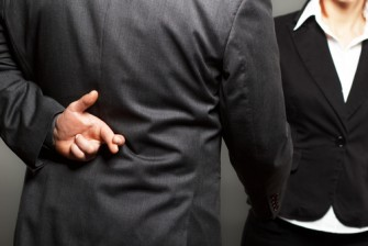 businessman with fingers behind back