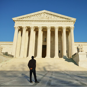 A man standing in front of the supreme court building.