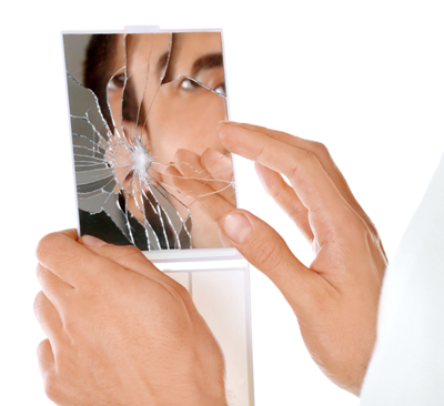 Man looking in smashed mirror