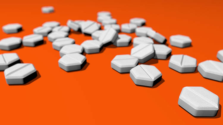 abortion medication on orange background