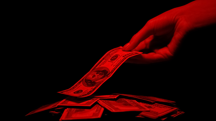 woman's hand taking a hundred dollar bill off a pile of money
