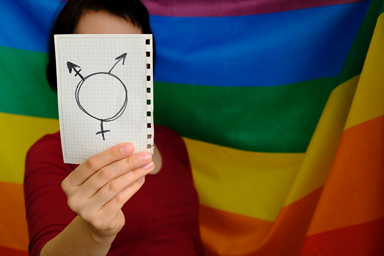 Person standing in front of a rainbow pride flag holding a piece of paper with a transgender symbol written on it in front of their face