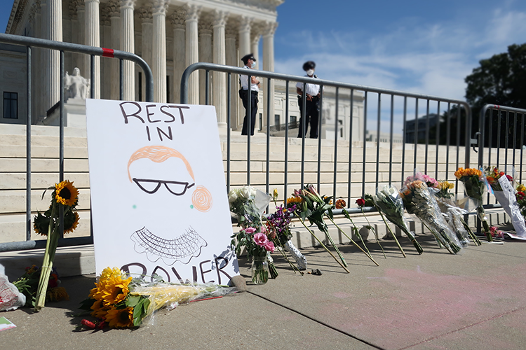 sign saying 'rest in power' outside the supreme court building with flowers