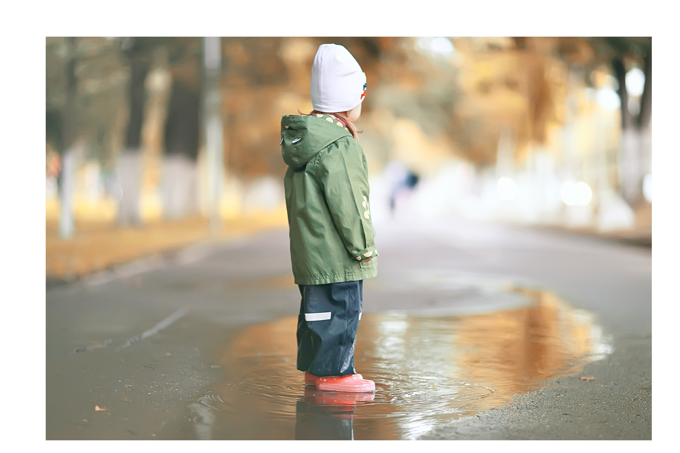 sad kid standing in puddle